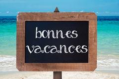 vacances-de-bonnes-signifiant-des-vacances-heureuses-écrits-sur-un-panneau-de-craie-en-bois-de-vintag-55716649